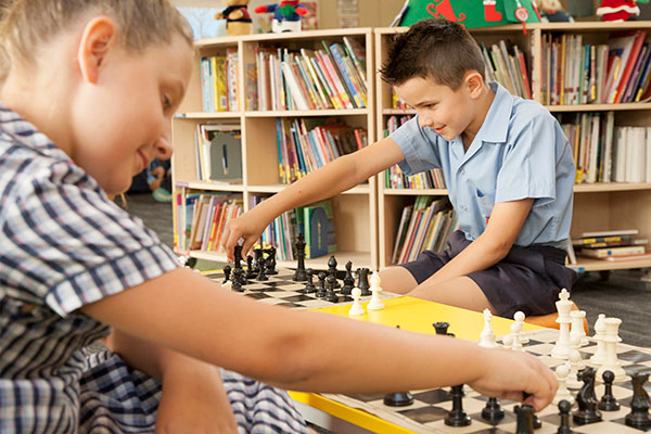 Two students playing chess in a library