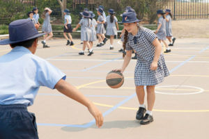 Students playing basketball outdoors
