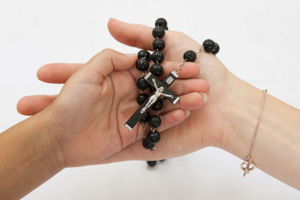 An adult and child hand together holding a rosary