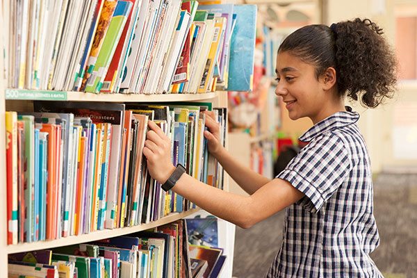 One girl in uniform looking through books in the library