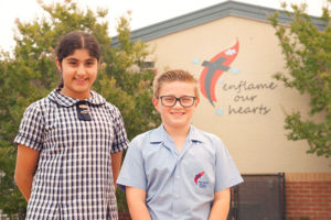 """Two students smiling and standing in front the school motto """"enflame our hearts"""""""
