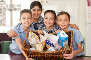 Four students smiling and showing a basket full of goods to give to charity