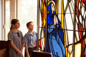 Two students admiring stained glass window in a church