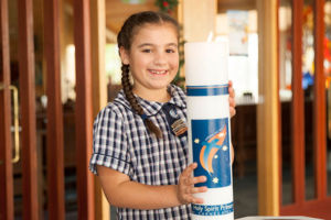 Young girl in uniform holding the school candle and smiling