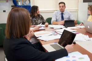 Staff members sitting at a table in discussion and using laptops and paper