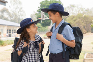 Two students with their school bags looking and smiling at each other