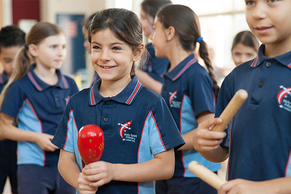 Children in sports uniforms playing instruments and smiling