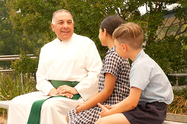 Principal Brother Nicholas of Holy Spirit Catholic Primary School sitting and chatting with two students